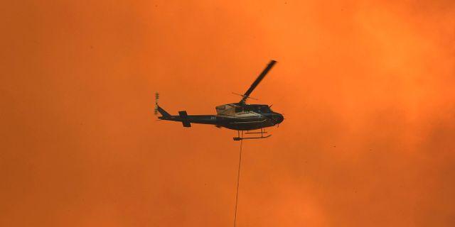 En helikopter vattenbombar en brand utanför staden Nana Glen.  WILLIAM WEST / AFP