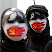 People wearing masks stand during a rally to show support for Uighurs and their fight for human rights in Hong Kong, Sunday, Dec. 22, 2019. Lee Jin-man / TT NYHETSBYRÅN