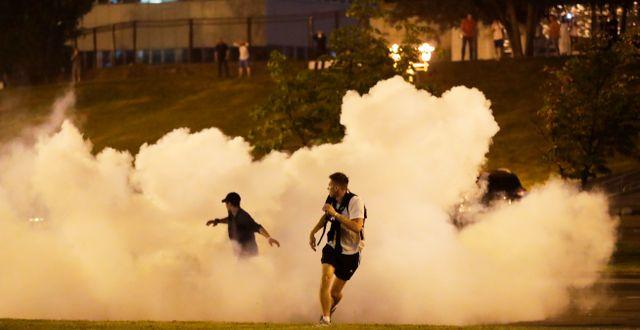 Demonstranter springer genom rök  Minsk. Sergei Grits / TT NYHETSBYRÅN