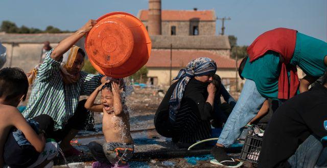 En kvinna tvättar en flicka i staden Mytilene på Lesbos där migranter sökt tillfälligt skydd efter lägerbranden. Petros Giannakouris / TT NYHETSBYRÅN
