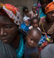 Kvinnor och barn väntar på hjälp efter att ha flytt attacken i Palma, Moçambique. Arkivbild.  TT NYHETSBYRÅN