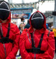 """Två besökare vid New York Comic Con utklädda till karaktärer från Netflix populära serie """"Squid Game"""".  Charles Sykes / TT NYHETSBYRÅN"""