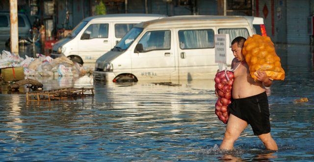 Man bär påsar med lökar genom vattenmassorna i Henanprovinsen i slutet av juli.  Dake Kang / TT NYHETSBYRÅN