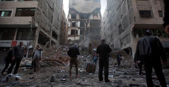 Palestinier vid en rasad byggnad i Gaza. Khalil Hamra / TT NYHETSBYRÅN/ NTB Scanpix