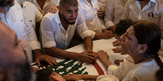 Människor sörjer på begravningen av en av brandmännen som dog i släckningsarbetet efter explosionen. Felipe Dana / TT NYHETSBYRÅN