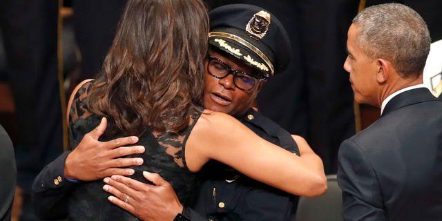 Michelle Obama omfamnar polischefen David Brown, Barack Obama till höger. Eric Gay / TT NYHETSBYRÅN