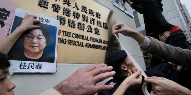 Demonstranter klistrar upp bilder på Gui Minhai på Kinas ambassad i Hongkong.  Vincent Yu / TT NYHETSBYRÅN/ NTB Scanpix