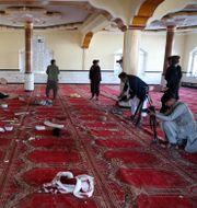 Afghanska journalister fotograferar i moskén efter bombdådet. Rahmat Gul / TT NYHETSBYRÅN