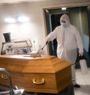 En person desinficerar en kista efter att en person dött med covid-19 i Belgien. Francisco Seco / TT NYHETSBYRÅN