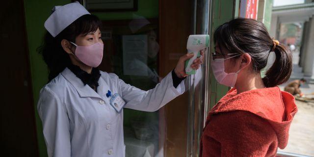 Sjukvårdspersonal mäter temperaturen på en kvinna i Pyongyang. KIM WON JIN / TT NYHETSBYRÅN