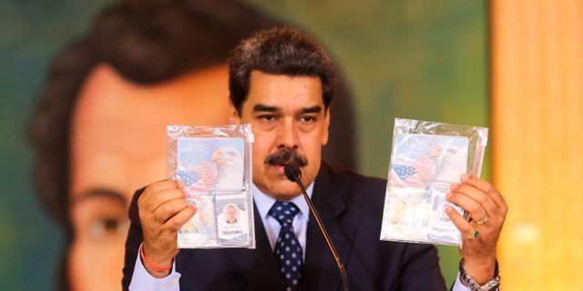 Venezuelas president Nicolas Madura visar upp vad som ska vara amerikanska pass efter den påstådda kuppen. TT NYHETSBYRÅN