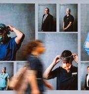 Kvinna i Melbourne passerar en vägg med bilder på personer i munskydd.  James Ross / TT NYHETSBYRÅN