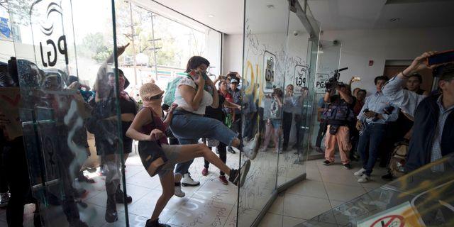 Demonstranter sparkar in dörrarna till säkerhetsdepartementet i staden. STRINGER / TT NYHETSBYRÅN