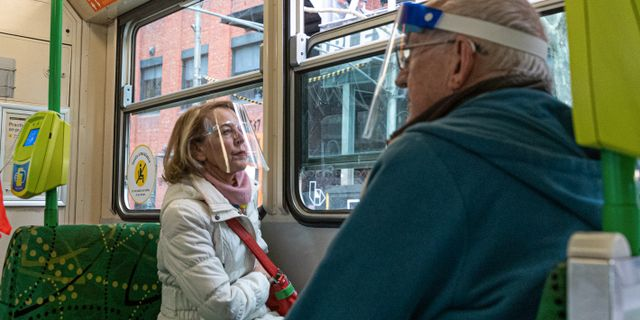 Två personer i visir i kollektivtrafiken i Australien. Asanka Brendon Ratnayake / TT NYHETSBYRÅN