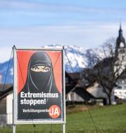 Heltäckande slöja kopplas samman med extremism på förbudssidans affischer. Urs Flüeler/AP/TT