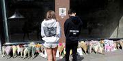 Personer framför blommor för att hedra terrordådets offer.  Darren Staples / TT NYHETSBYRÅN