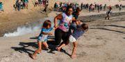 En familj flyr undan tårgasen vid gränsövergången i mexikanska Tijuana.  Kim Kyung Hoon / TT NYHETSBYRÅN