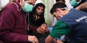 Personal behandlar en pojke efter den misstänkta gasattacken. Bilden är släppt av den statliga nyhetsbyrån Sana. TT NYHETSBYRÅN/ NTB Scanpix
