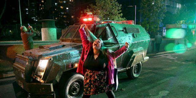 En kvinna skriker åt polisen under protesterna mot höjda priser på tunnelbanebiljetter i Santiago under fredagen. Esteban Felix / TT NYHETSBYRÅN