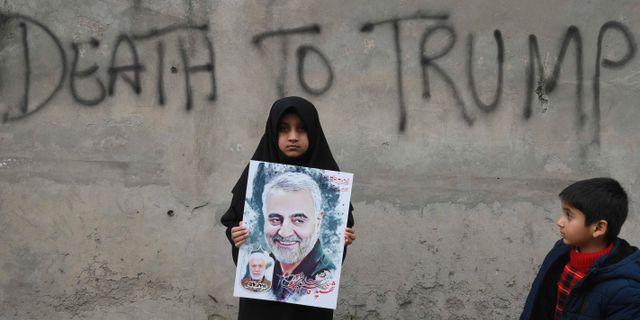 En flicka med ett plakat med Qassem Soleimanis porträtt. ARIF ALI / AFP
