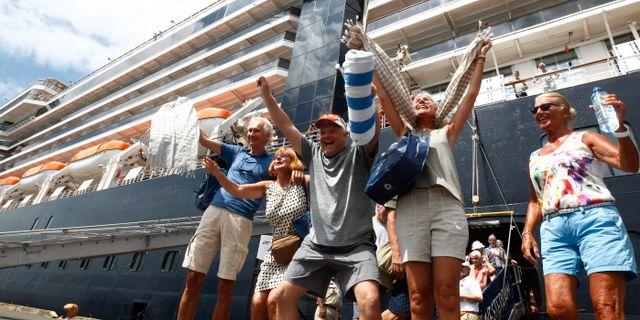 Passagerare jublar efter att ha fått lämna Westerdam. Personerna på bilden har inget med texten att göra. Heng Sinith / TT NYHETSBYRÅN