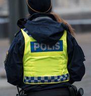 Ryggen på en polis. Arkivbild. Johan Nilsson/TT / TT NYHETSBYRÅN
