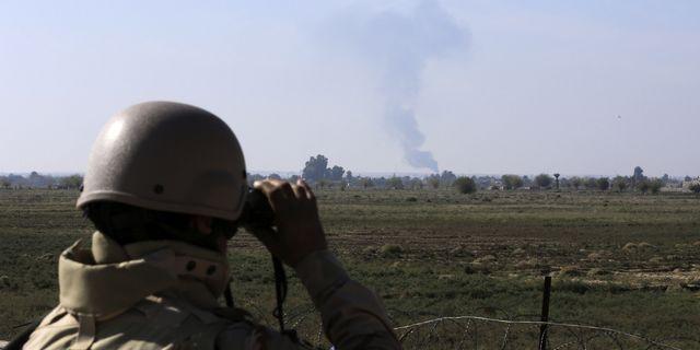 En irakisk soldat blickar ut över rök från en USA-ledd flygattack. Spänningarna i regionen har ökat i och med konflikten mellan USA och Iran. TT