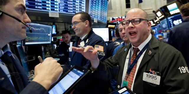Handlaren Jeffrey Vazquez (till höger) ropar på börsgolvet i New York på fredagen.  Richard Drew / TT NYHETSBYRÅN