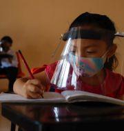 Arkivbild: 10-åriga Jade Chan Puc skriver under sin första dag tillbaka i skolan i våras, efter ett års distansundervisning.  Martin Zetina / TT NYHETSBYRÅN
