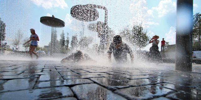 Barn svalkar sig i duschar i Vilnius.  PETRAS MALUKAS / AFP