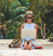En kvinna arbetar från stranden. Shutterstock/Roma Black