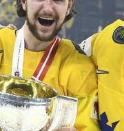 Sveriges Viktor Arvidsson, Filip Forsberg och Mattias Ekholm med sina guldmedaljer och segerpokalen efter segern i finalen i ishockey-VM mellan Sverige och Schweiz i Royal Arena.  Claudio Bresciani/TT / TT NYHETSBYRÅN