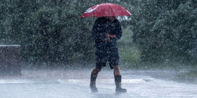 Man med gummistövlar och paraply. Johan Nilsson/TT / TT NYHETSBYRÅN