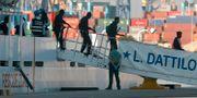 Migranter går av det italienska fartyget i hamnen i Valencia.  PAU BARRENA / AFP
