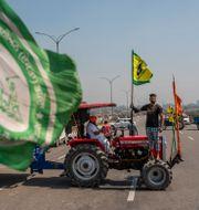 Lantbrukare blockerar väg med traktor. Altaf Qadri / TT NYHETSBYRÅN