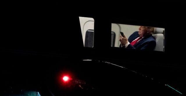 Donald Trump tittar på en telefon ombord på helikoptern Marine One utanför Vita huset på fredagen.  Andrew Harnik / TT NYHETSBYRÅN