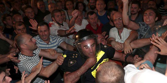 Demonstranter går till attack mot en polisman i Tbilisi i Georgien.  IRAKLI GEDENIDZE / TT NYHETSBYRÅN