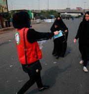 Kvinna delar ut munskydd till pilgrimer.  Khalid Mohammed / TT NYHETSBYRÅN