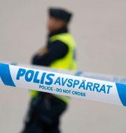 En polisman och ett avspärrningsband. Johan Nilsson/TT / TT NYHETSBYRÅN
