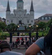 Människor blickar ut mot den mörka himlen över New Orleans i väntan på Barry. SETH HERALD / AFP