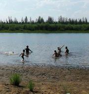 Barn leker i en sjö utanför staden Verchojansk i den ryska delrepubliken Sacha i Sibirien Olga Burtseva / TT NYHETSBYRÅN