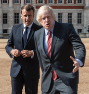 En person går bakom en EU-flagga samt Macron och Johnson.  TT