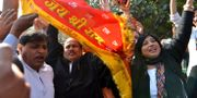 Människor vevar med en flagga som hyllar guden Rama, som enligt hinduerna föddes på platsen. TT NYHETSBYRÅN