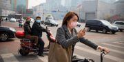 Människor med munskydd i Peking. Mark Schiefelbein / TT NYHETSBYRÅN