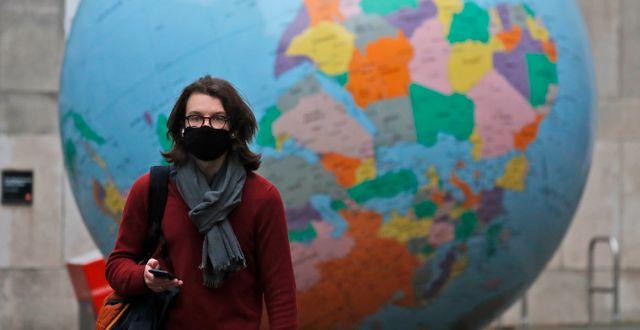 En kvinna med munskydd går förbi en stor jordglob utanför London School of Economics i London.  Frank Augstein / TT NYHETSBYRÅN