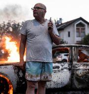 Jacob Simona står intill sin brinnande bil i Lod på tisdagen. Heidi levine / TT NYHETSBYRÅN