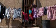 En kvinna och ett barn sitter vid ytterdörren i Johannesburg den 16 april. Themba Hadebe / TT NYHETSBYRÅN