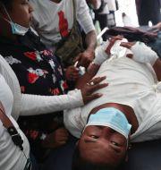 En skadad demonstrant får vård, 26 februari. TT NYHETSBYRÅN