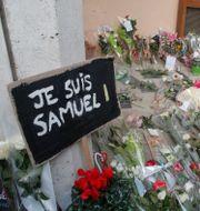 Ett blomsterhav utanför skolan och en skylt med texten: Jag är Samuel. Michel Euler / TT NYHETSBYRÅN