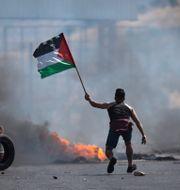 En demonstrant med en palestinsk flagga utanför staden Nablus på fredagen. Majdi Mohammed / TT NYHETSBYRÅN